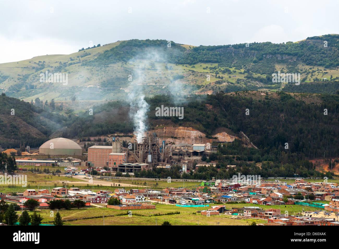Una fábrica que produce contaminación cerca de un pequeño pueblo Imagen De Stock
