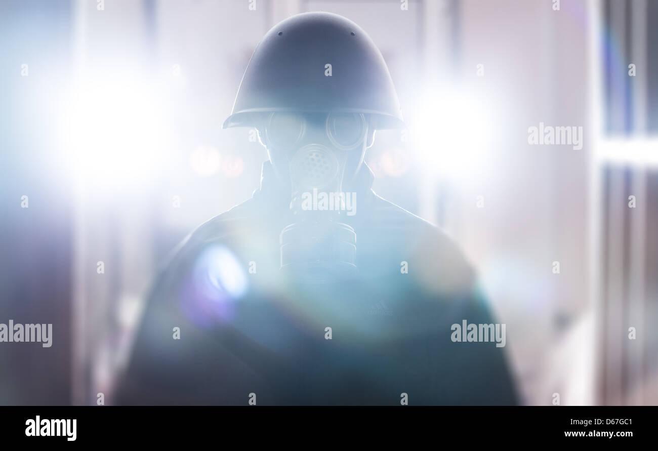 Un hombre en casco militar y máscara de gas Imagen De Stock
