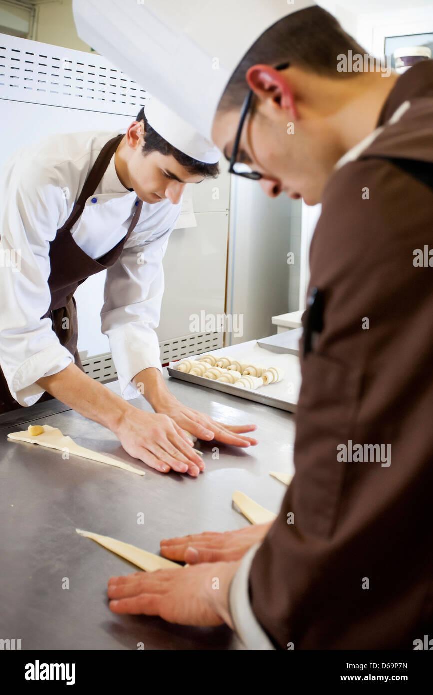Los panaderos la conformación de la masa en la cocina Imagen De Stock