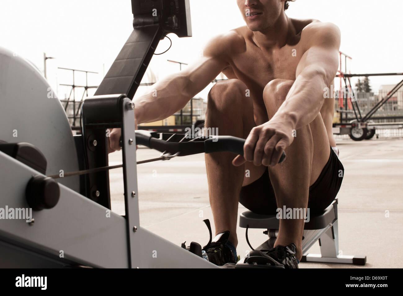 Hombre utilizando equipo de ejercicio en el gimnasio Imagen De Stock