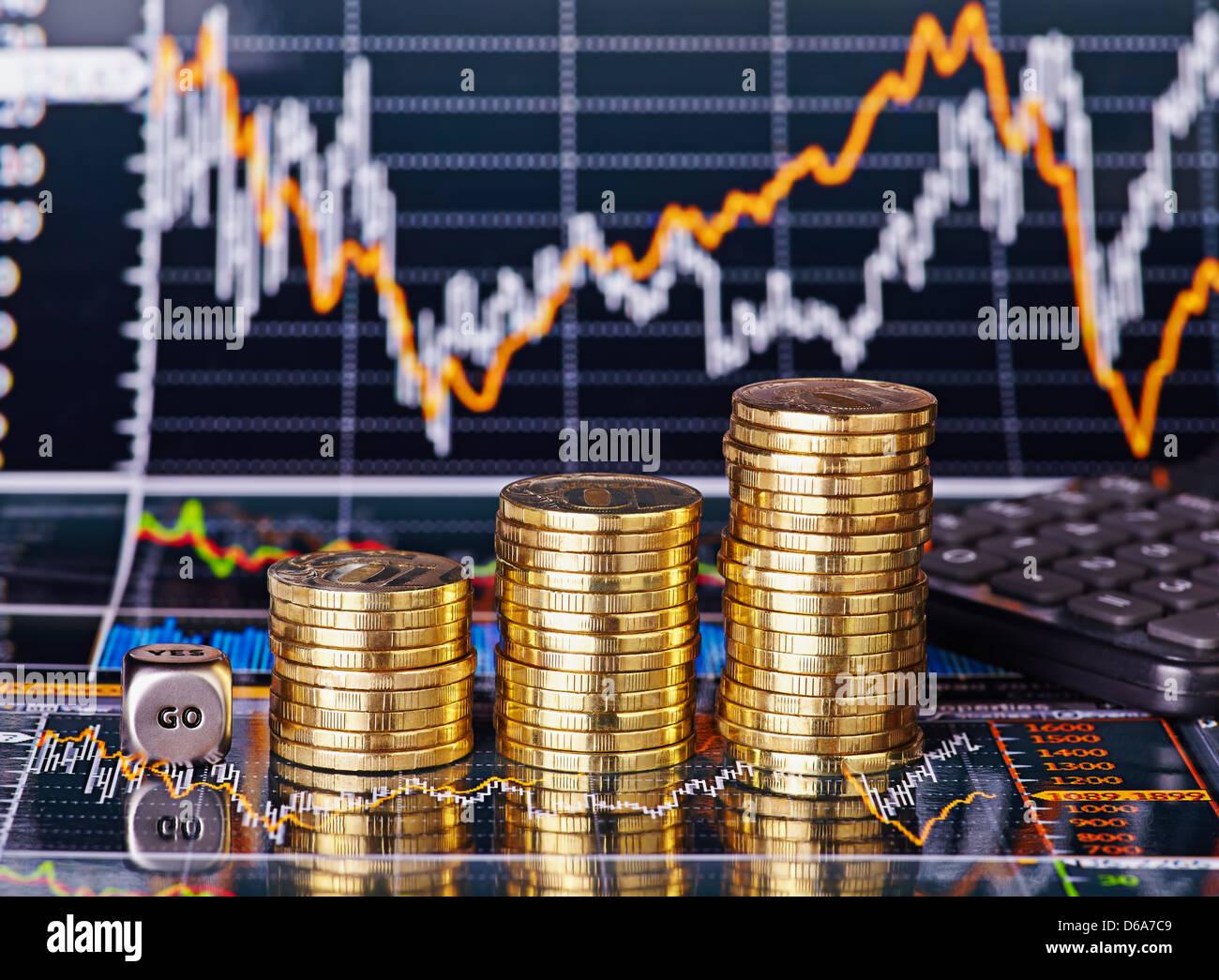 Subida apila monedas, cubos cubo con la palabra GO y calculadora de los gráficos de cotizaciones financieras como fondo. Enfoque selectivo Foto de stock