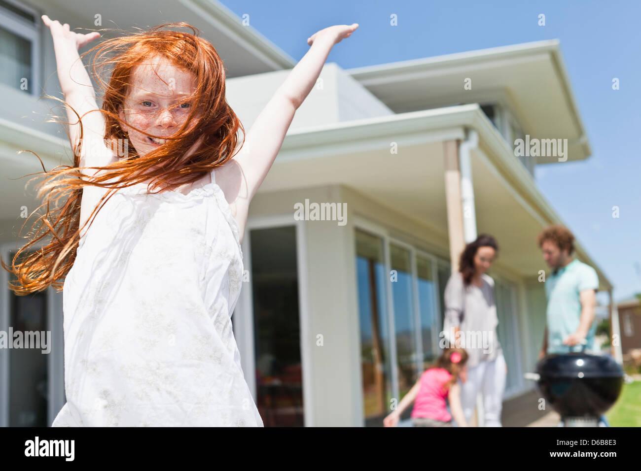 Chica sonriente aclamando en el patio Imagen De Stock