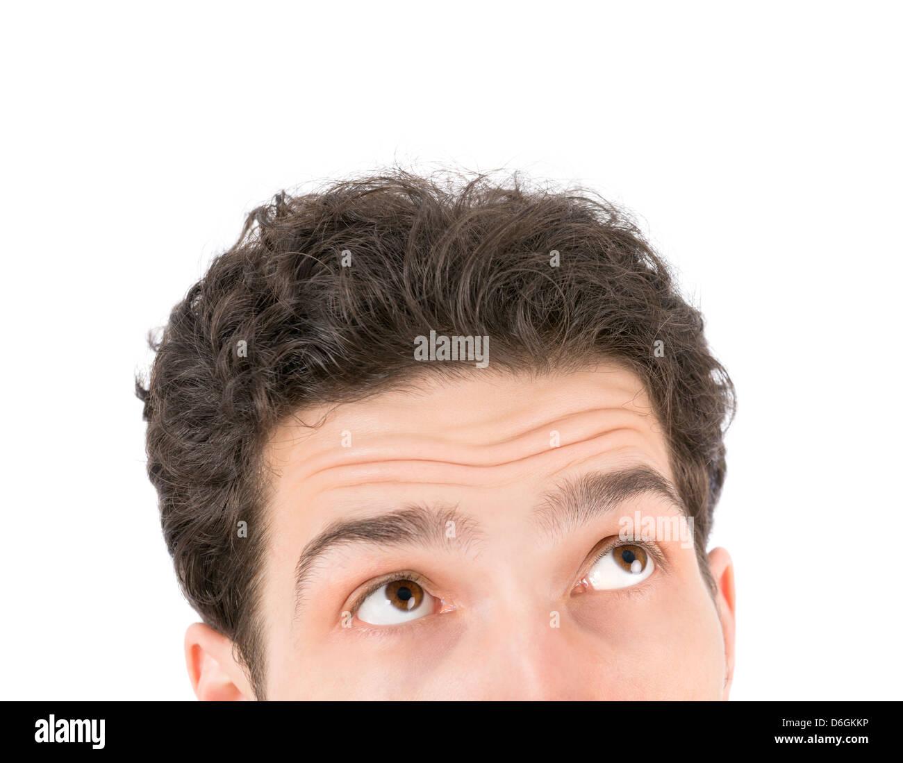 Retrato de un joven apuesto hombre mirando hacia arriba. Aislado sobre fondo blanco. Imagen De Stock