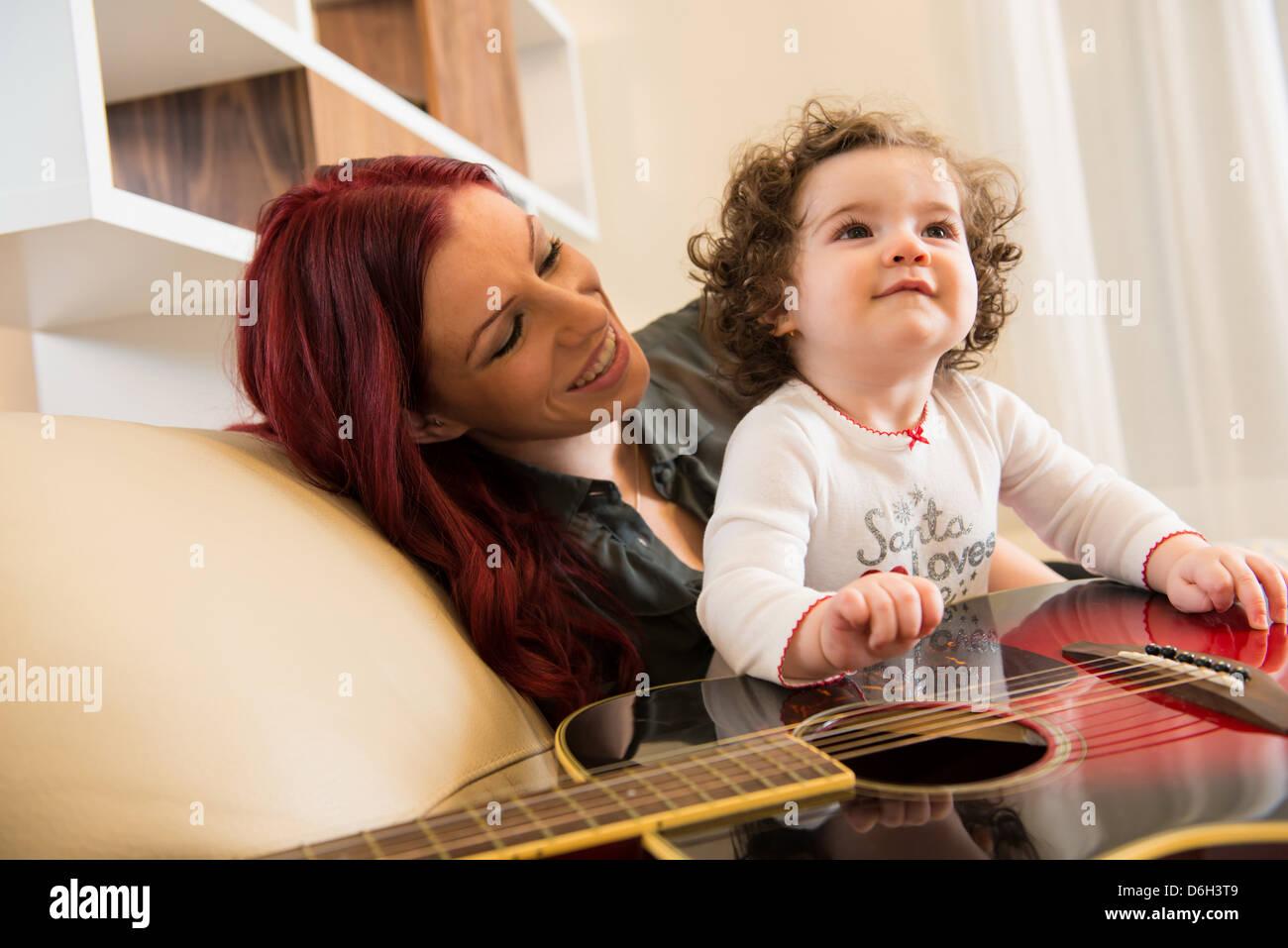 Madre e hija con guitarra en el sofá Foto de stock