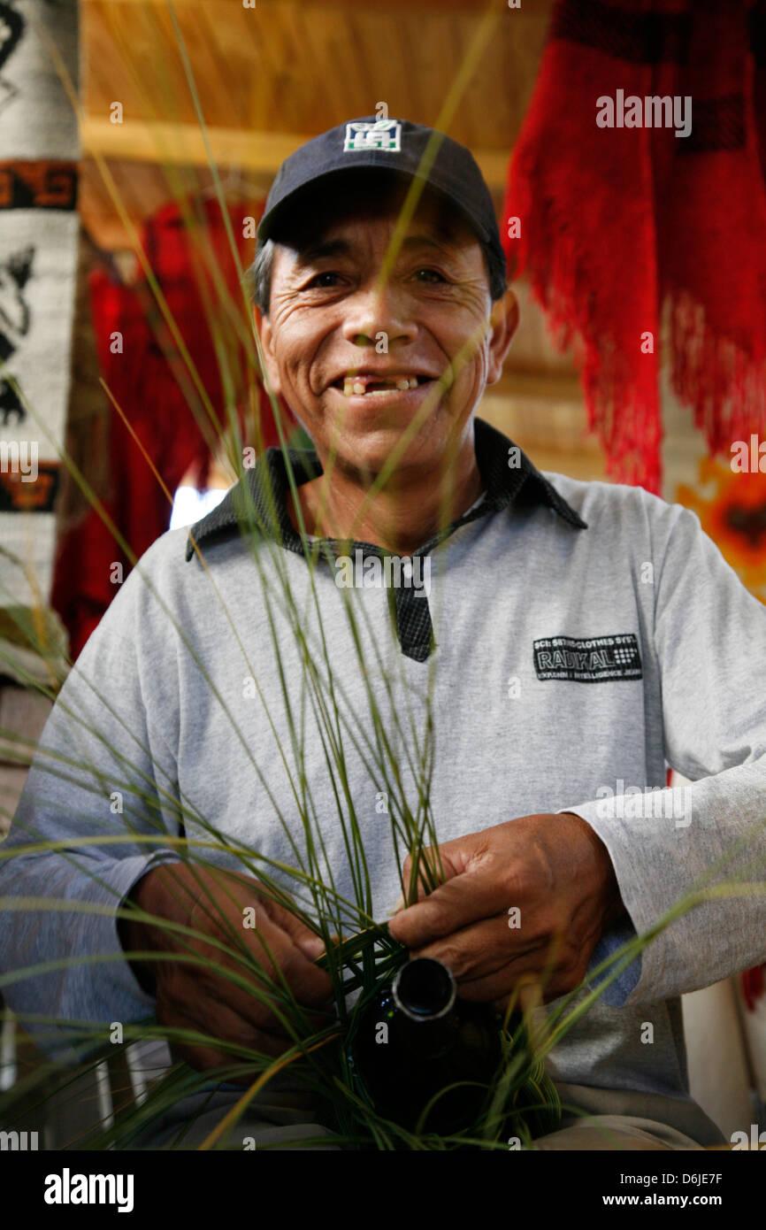 Retrato de un hombre Quechua tejiendo con hojas de palma en el mercado de Cafayate, Provincia de Salta, Argentina, Imagen De Stock