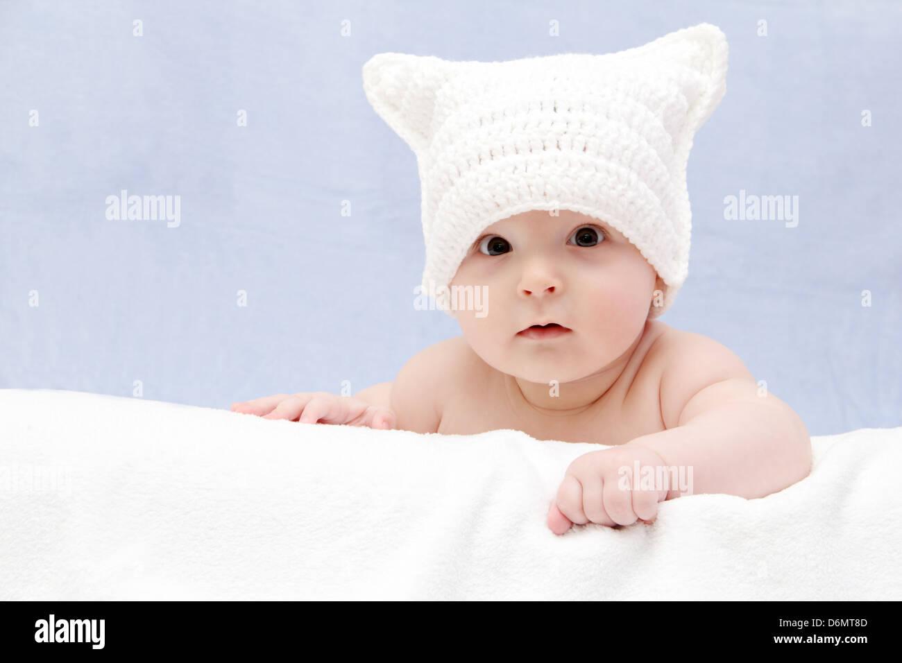 Hermoso bebé en white hat radica en la cama Imagen De Stock