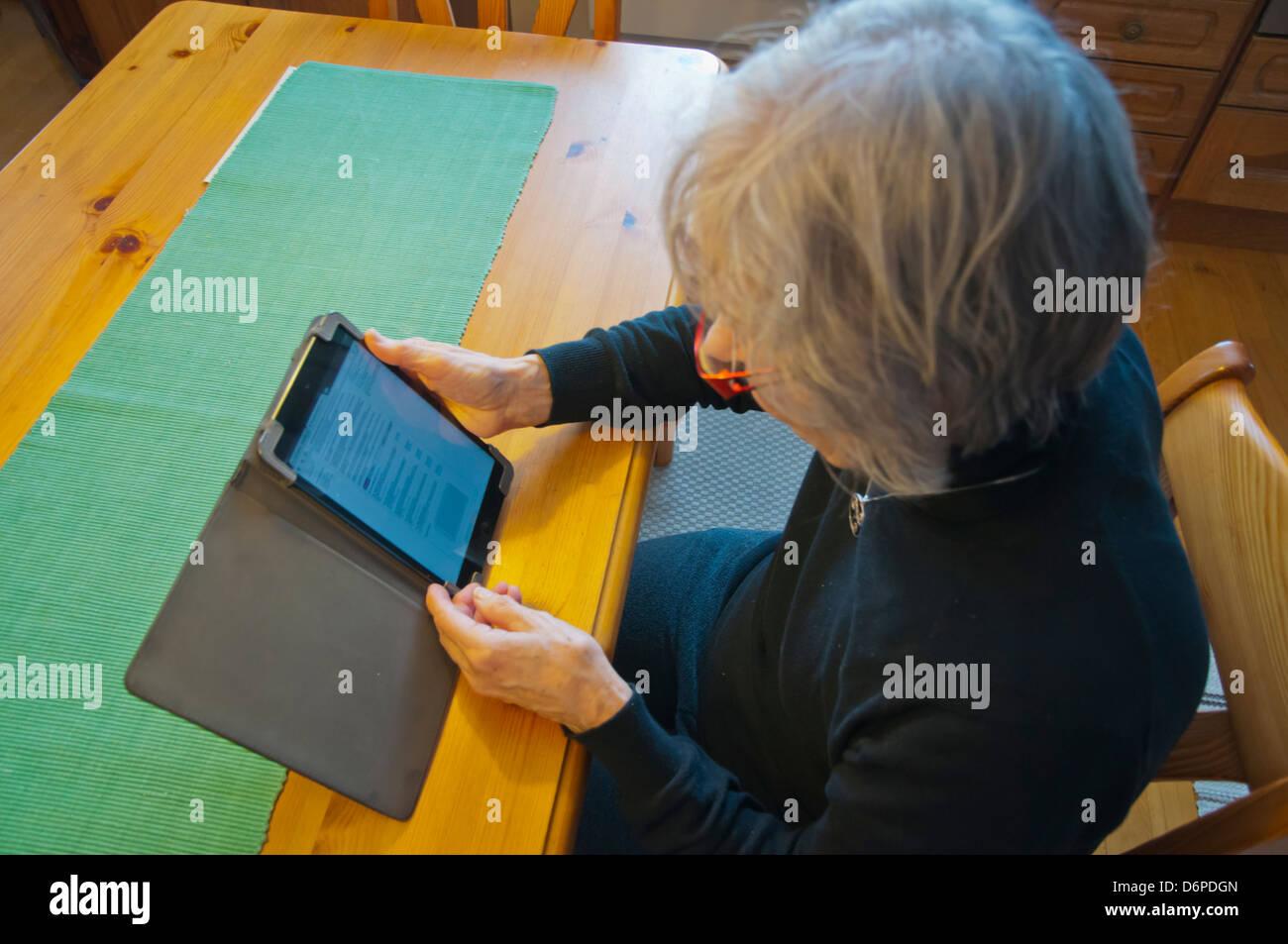Mujer en sus primeros 70s usa mini ipad Pori Finlandia Europa Imagen De Stock