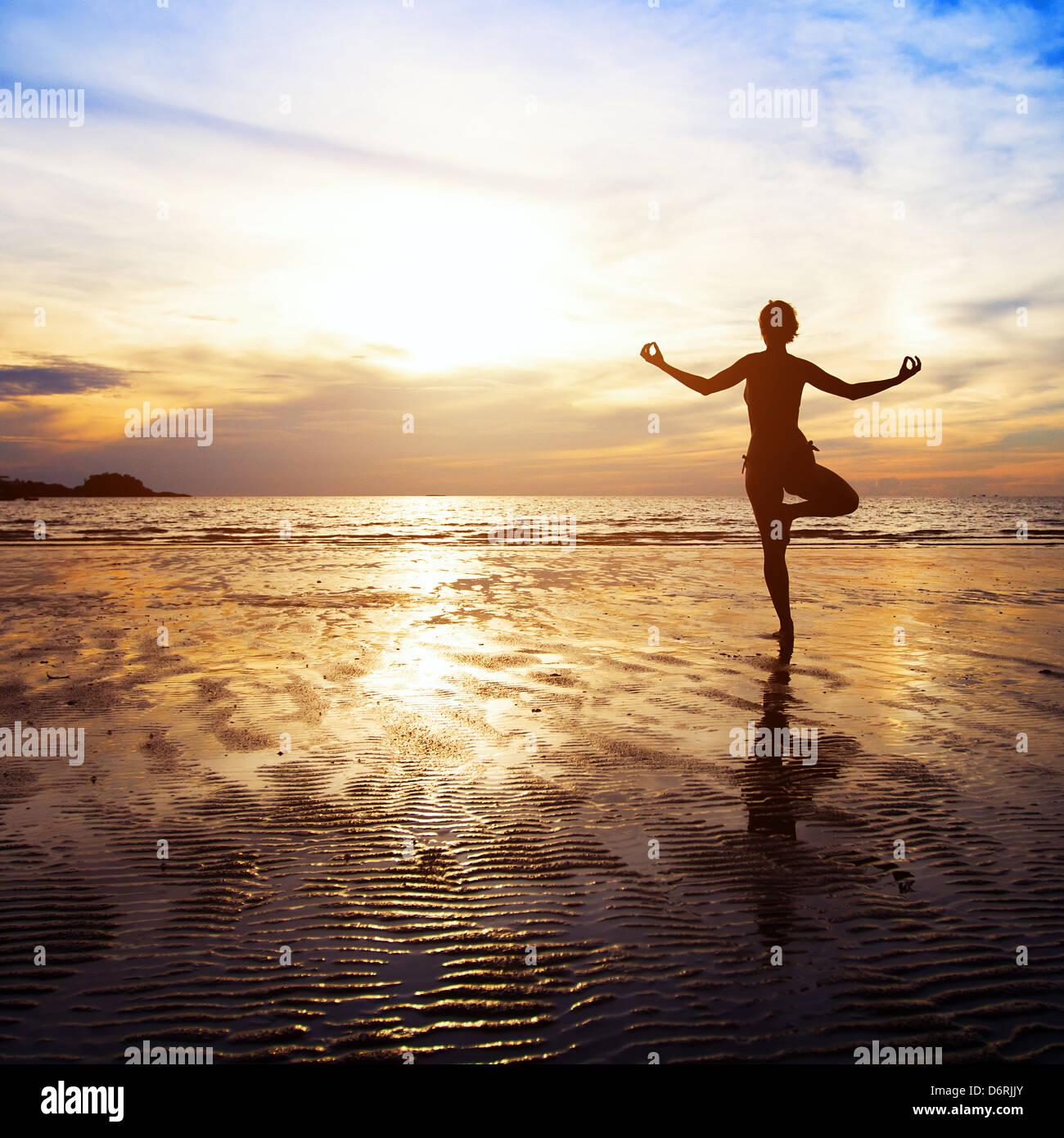 Concepto de bienestar, la hermosa puesta de sol en la playa, mujer practicando yoga Imagen De Stock