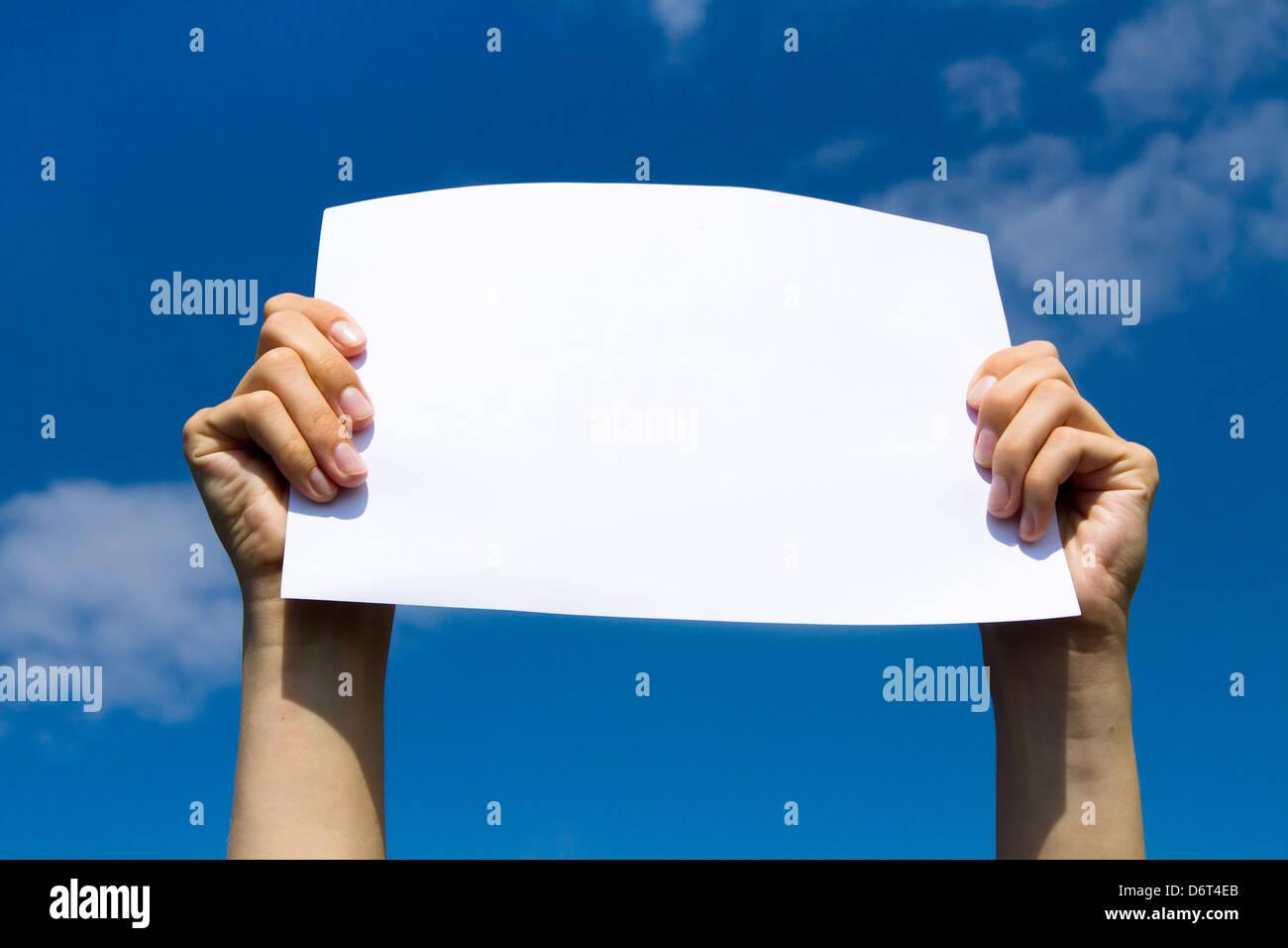 Página en blanco en manos sobre fondo de cielo azul Imagen De Stock