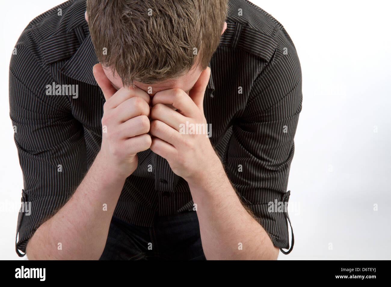 El hombre con la cabeza entre las manos Imagen De Stock
