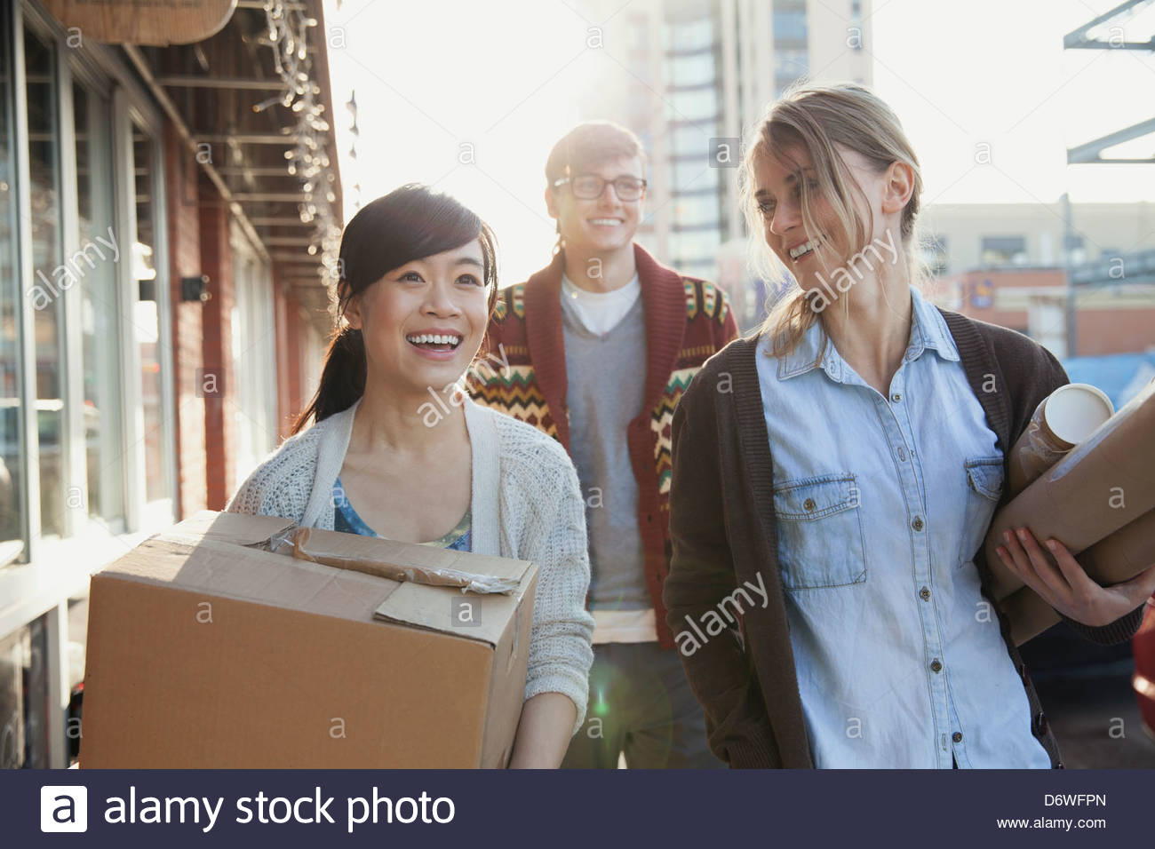 Los profesionales del diseño felices llevando paquetes Imagen De Stock