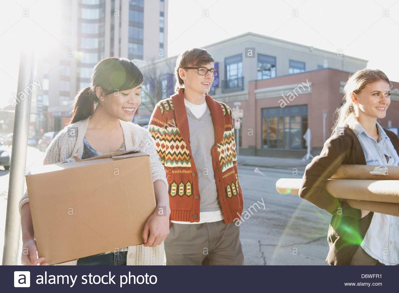 Los profesionales del diseño felices llevando paquetes con edificios en segundo plano. Imagen De Stock