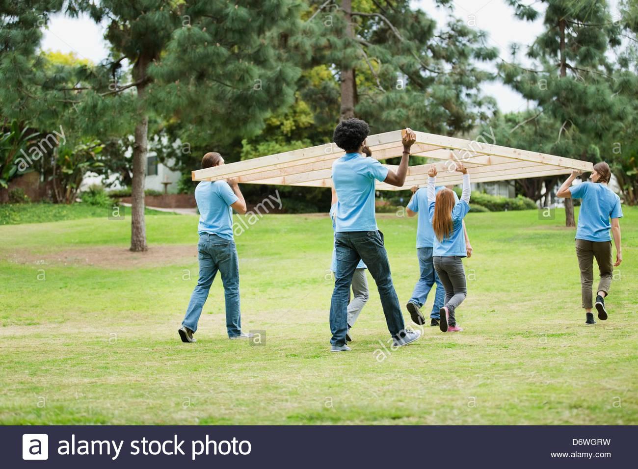 Vista trasera de voluntarios llevando armadura de madera en el parque Imagen De Stock