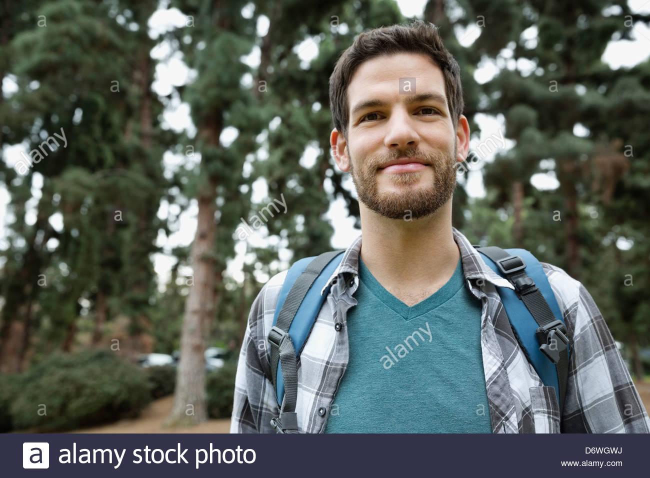 Retrato de un hombre adulto medio guapo con mochila en el bosque Imagen De Stock