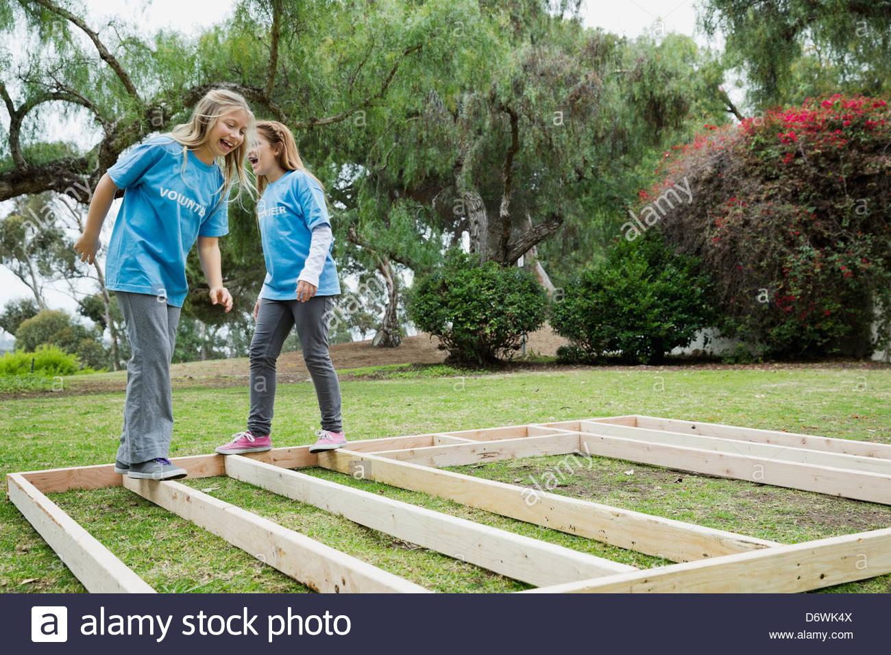 Poco alegres chicas jugando con marco de madera en el parque Imagen De Stock