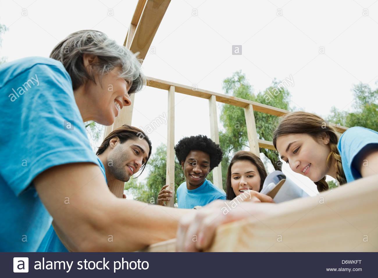 Ángulo de visión baja de voluntarios revisar lista de comprobación mientras decisiones marco de madera Imagen De Stock