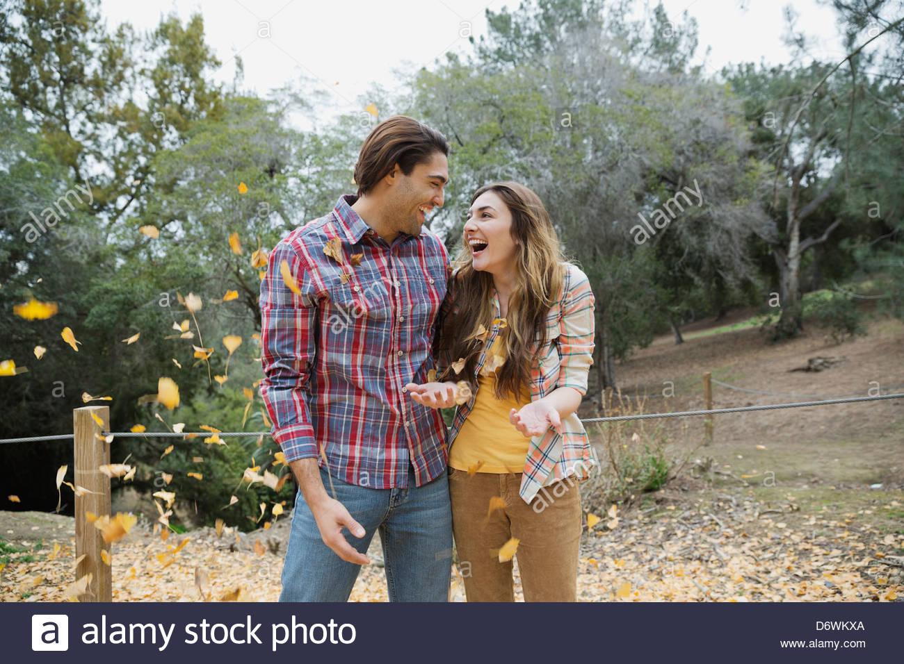 Pareja joven alegre mirarse mientras juega con las hojas de otoño en el parque Foto de stock