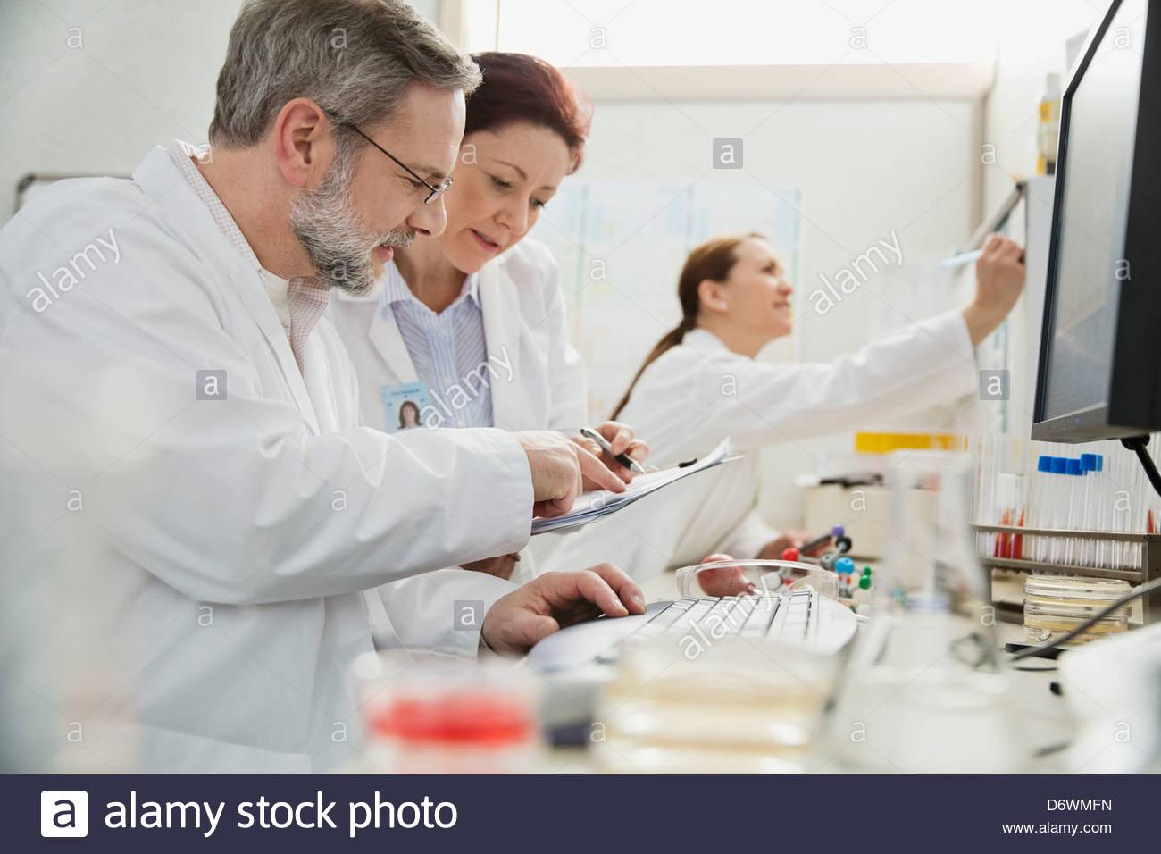 Macho y hembra de profesionales médicos que trabajan en el laboratorio Imagen De Stock