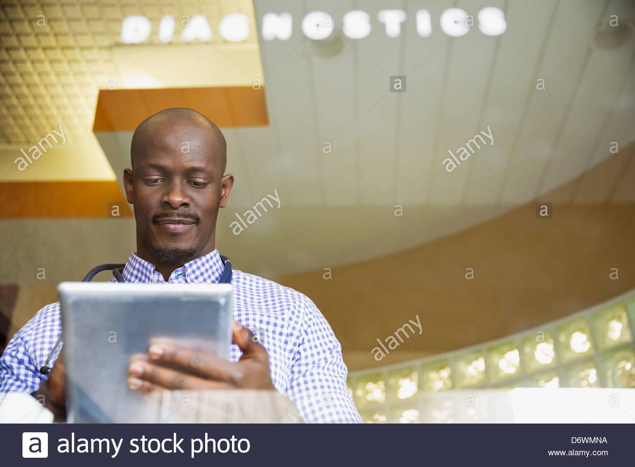 Mitad macho adulto médico utilizando tablet digital en la clínica Imagen De Stock