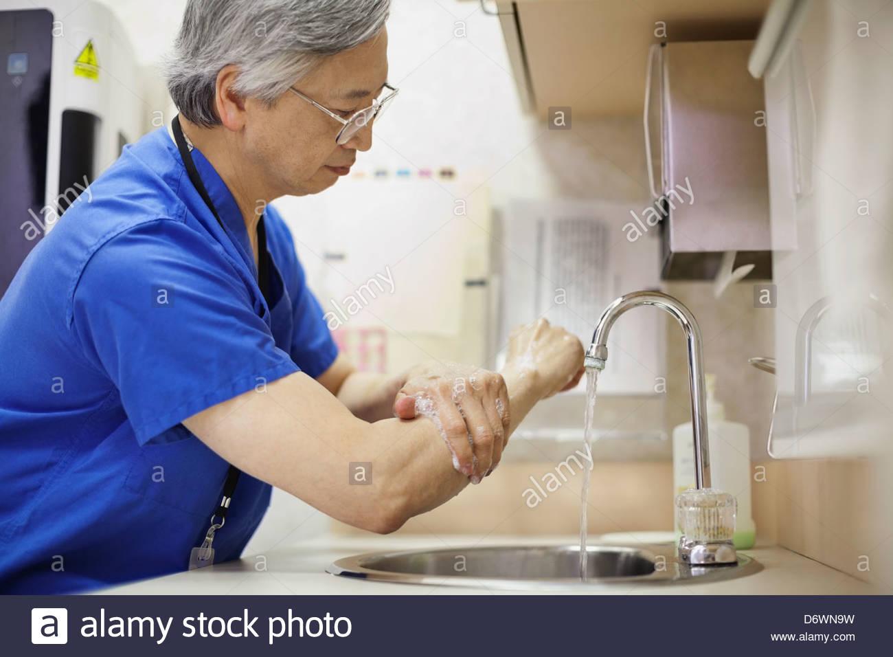 Vista lateral del médico varón el lavado de manos Foto de stock