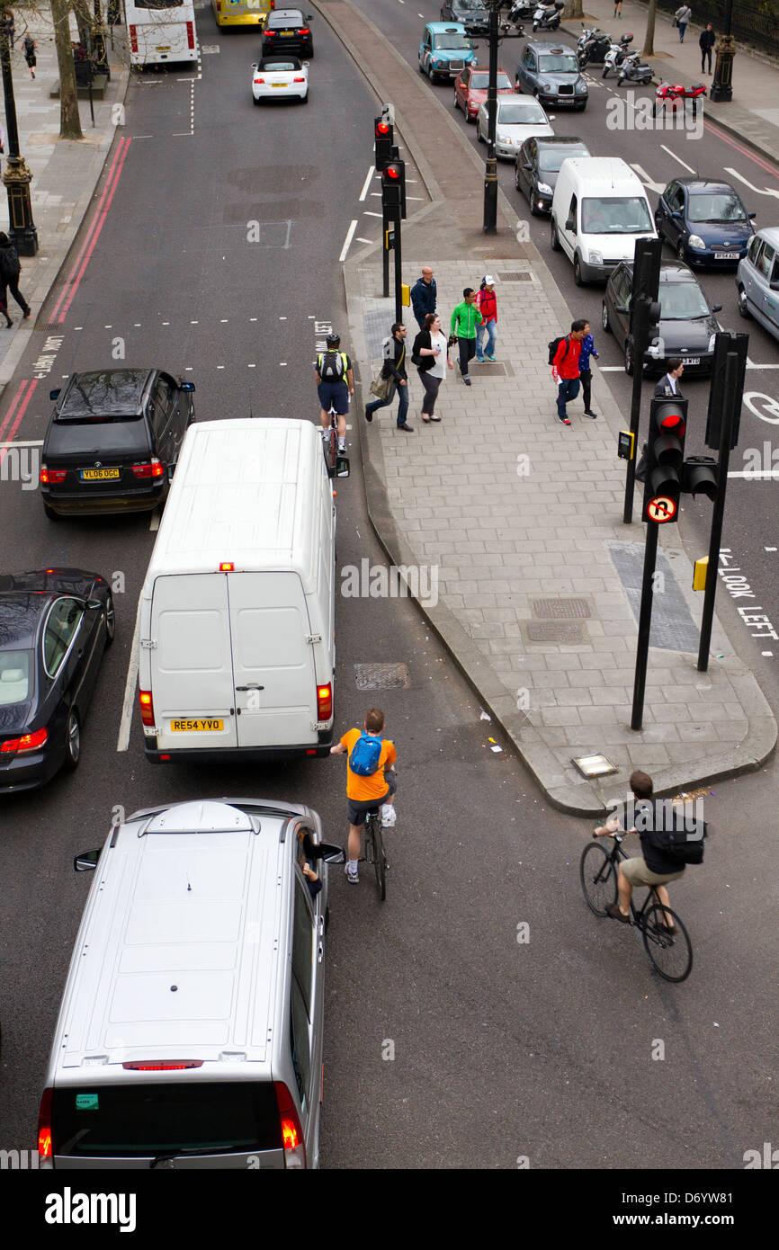Vehículos y ciclistas parado en el semáforo en una luz roja en Londres, Inglaterra, Reino Unido. Imagen De Stock