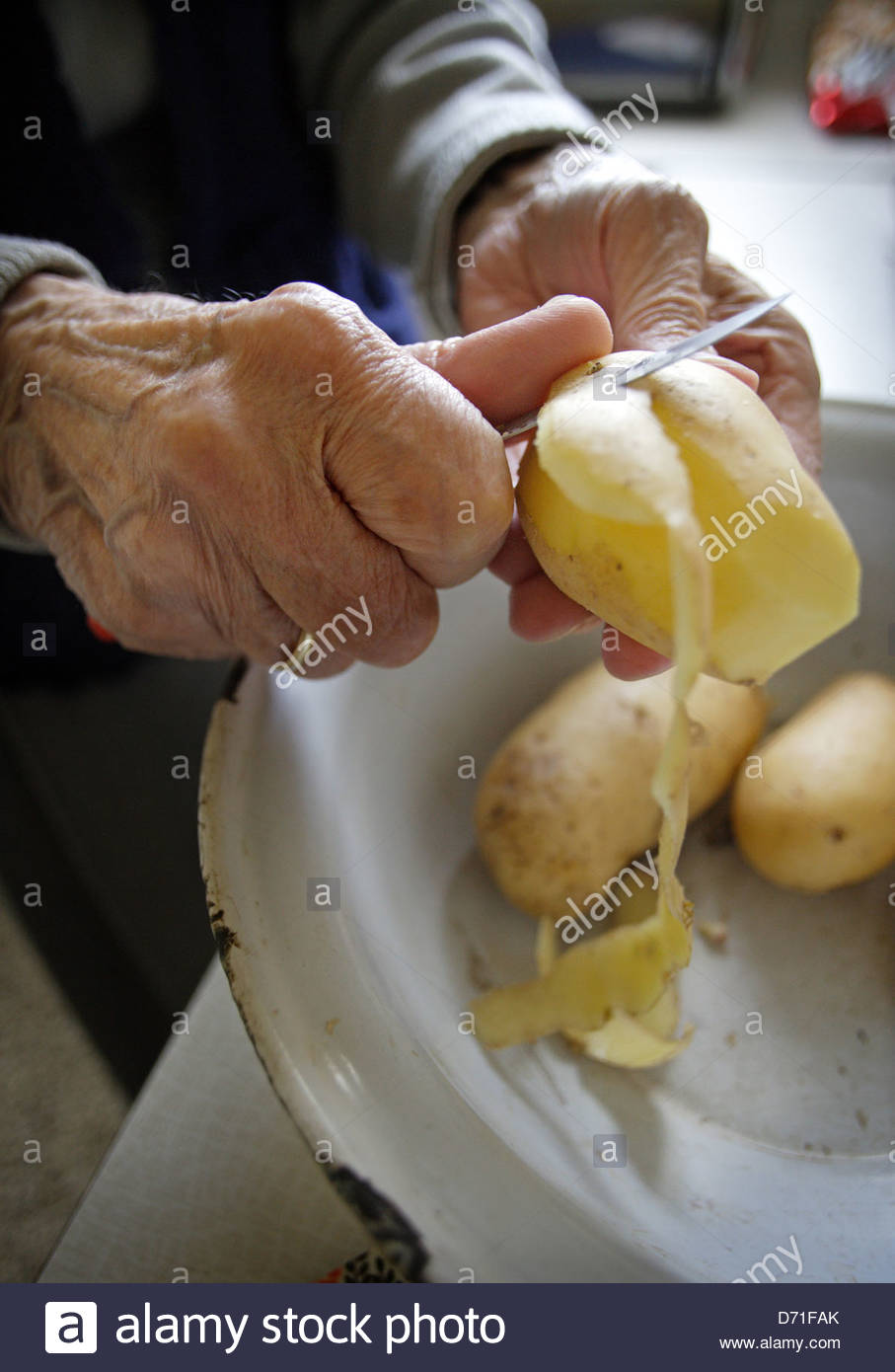 Mujer Senior pelando patatas en la cocina Imagen De Stock