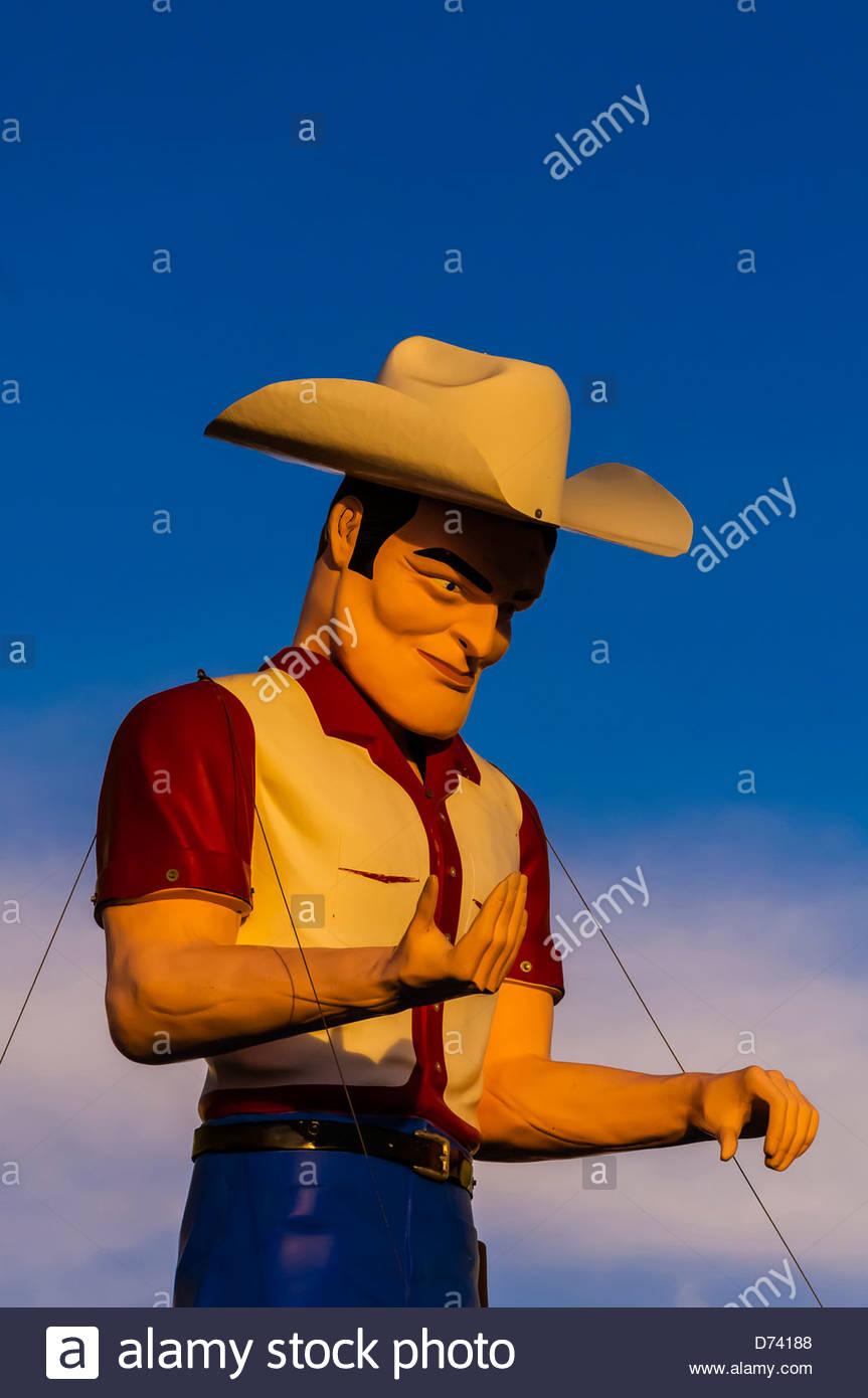 """""""Un gran hombre uffler cowboy encima de John's autos usados, la histórica Ruta 66, Gallup, Nuevo México, EE.UU.. Foto de stock"""