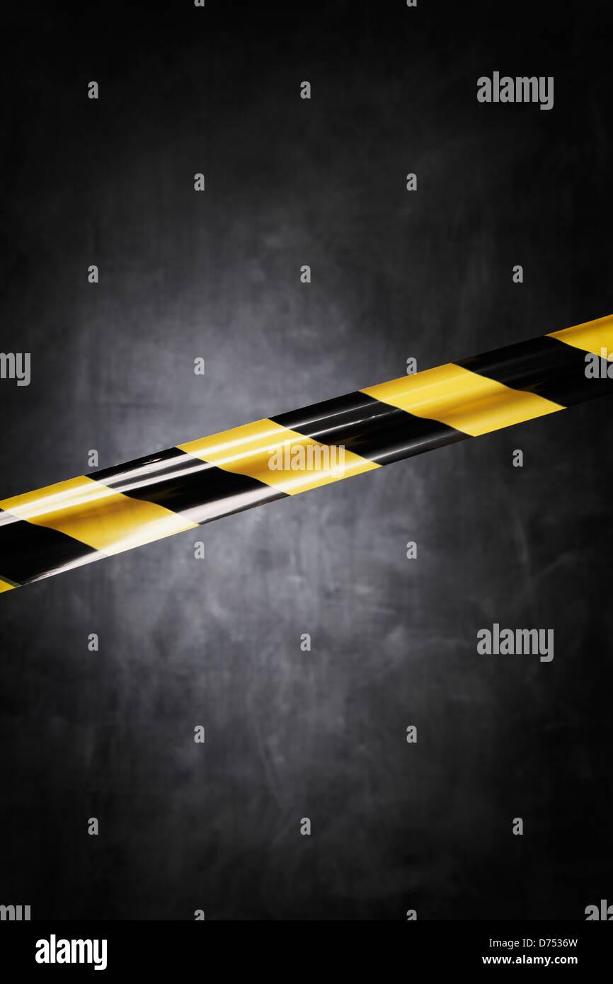 Barrera de plástico amarillo y negro cinta bloqueando el camino. Imagen De Stock