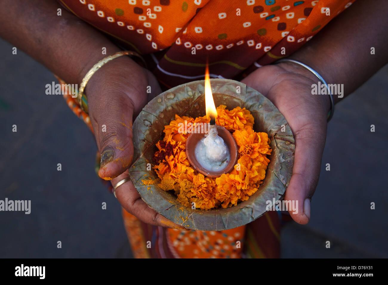 Una mujer sostiene puya pooja ofrendas con flores y velas en el río Ganges en Varanasi, India. Imagen De Stock