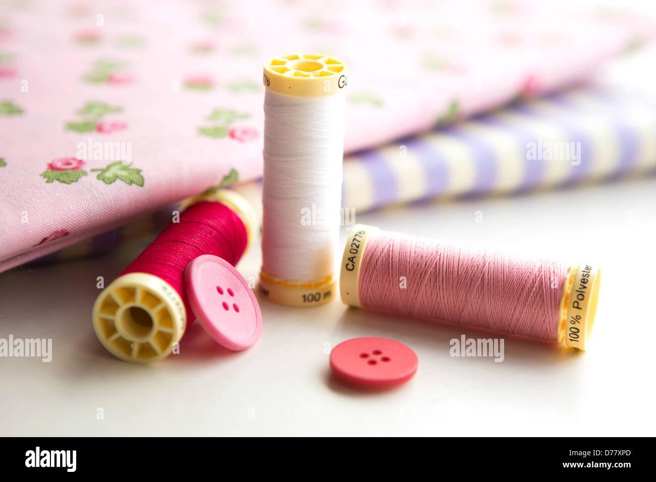 Accesorios - hilo de costura, tejido y botones colocados sobre un fondo gris claro Foto de stock