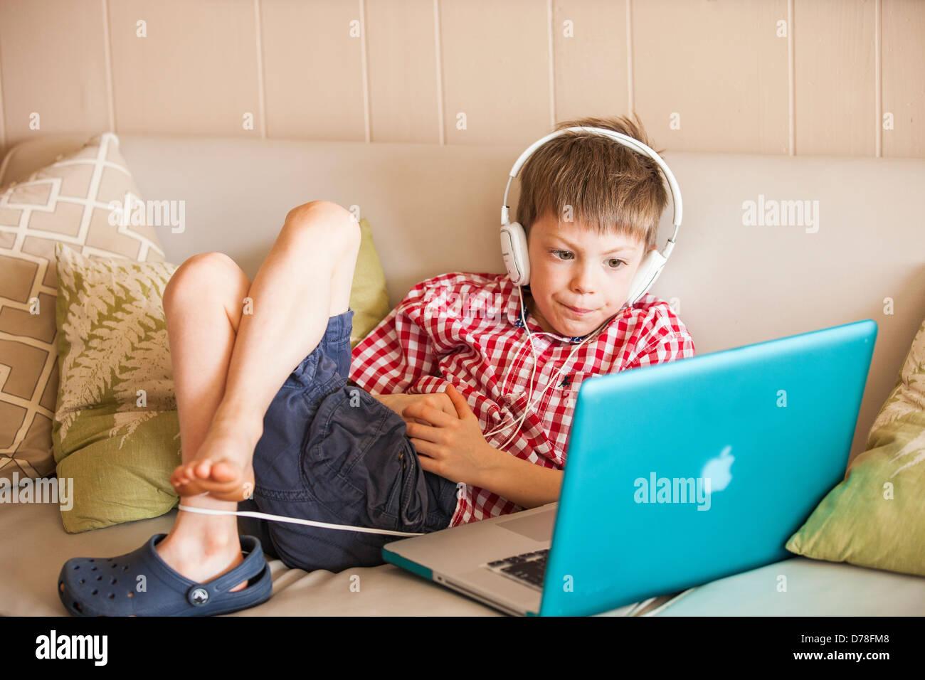 Niño con ordenador portátil y auriculares Imagen De Stock