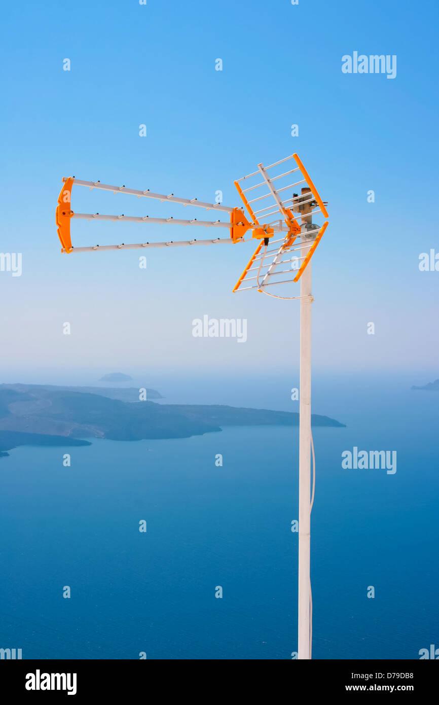 Naranja grande con antena de TV blanco contra el mar Egeo y parte del  volcán en la isla de Santorini, Grecia en Fira Fotografía de stock - Alamy