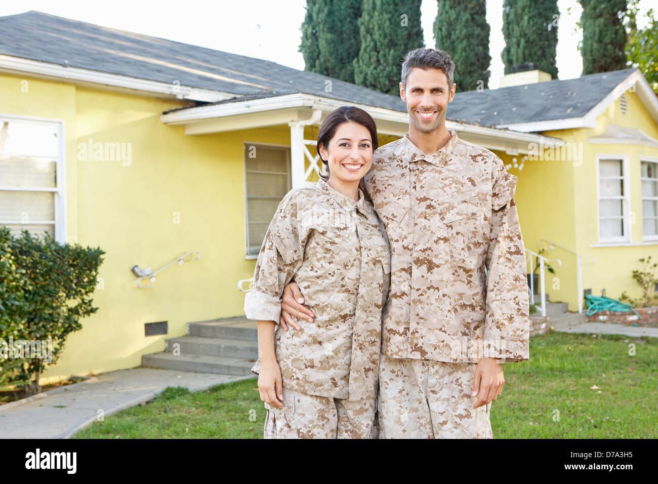 Pareja de militares en uniforme de pie fuera de casa Imagen De Stock