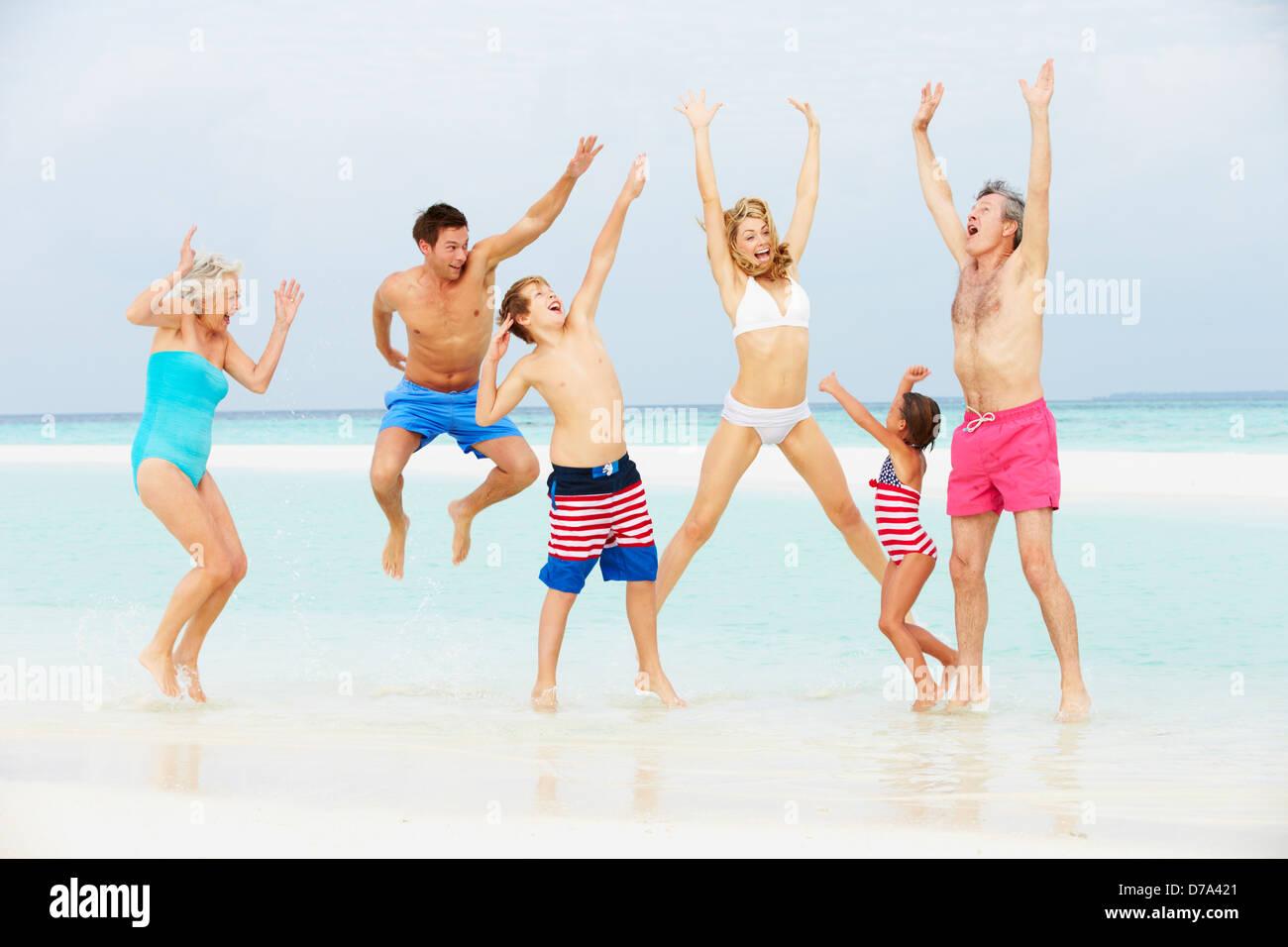 Generación de múltiples familia divirtiéndose en el mar en la playa de vacaciones Foto de stock