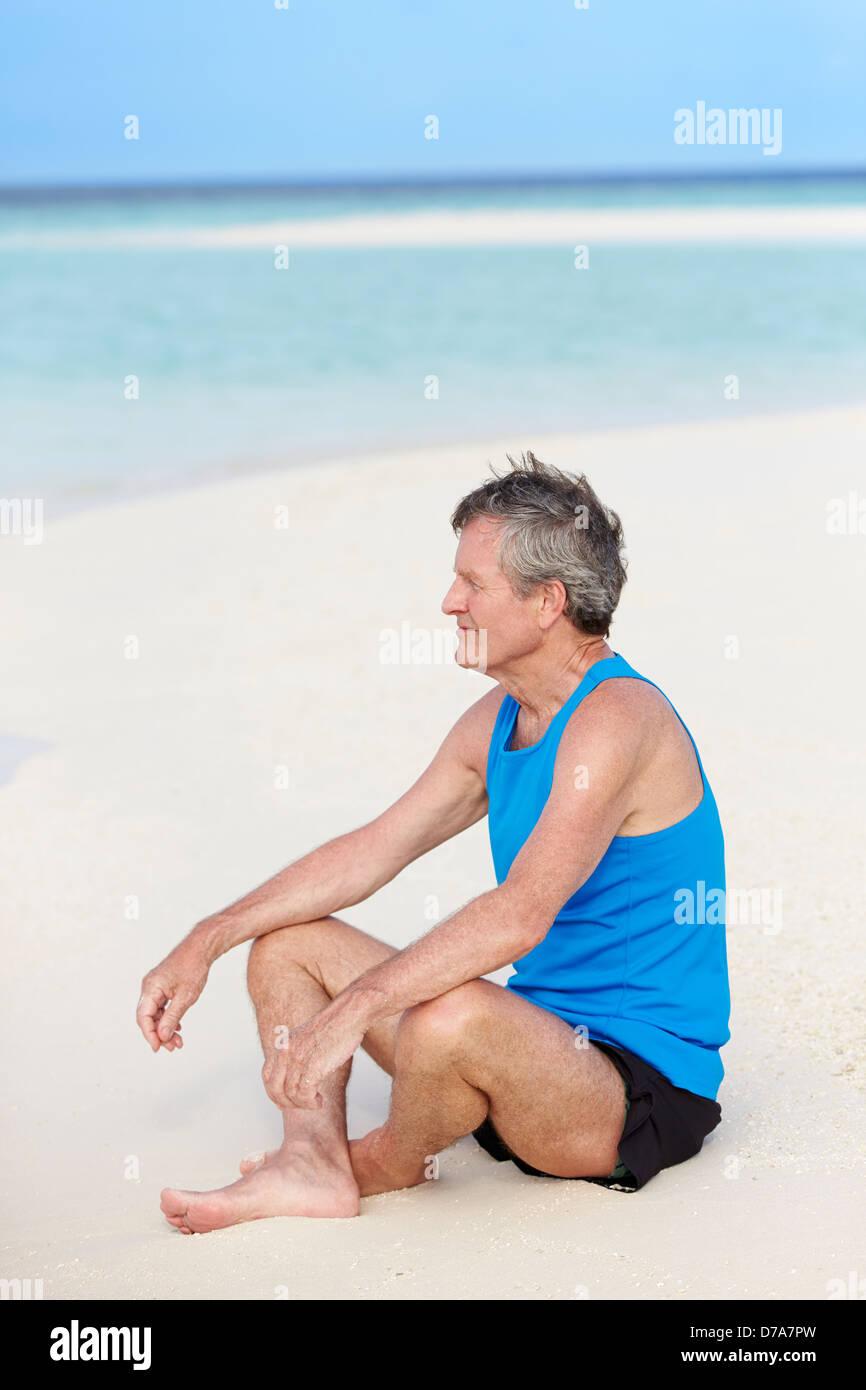 Hombre senior en ropa deportiva relajante en Playa Hermosa Imagen De Stock
