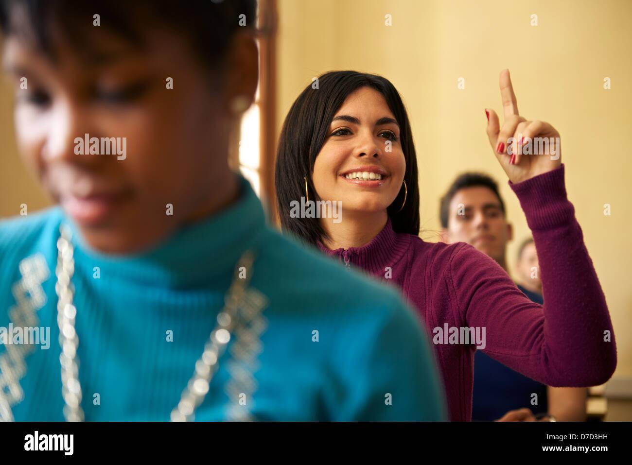Estudiantes en clase de la universidad con la mujer levantando la mano para realizar preguntas al profesor Imagen De Stock