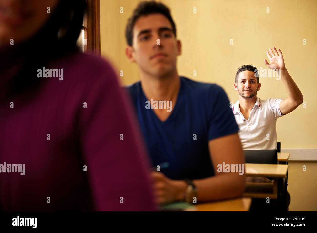 Estudiantes en clase de la universidad con el hombre levantando la mano para realizar preguntas al profesor Imagen De Stock