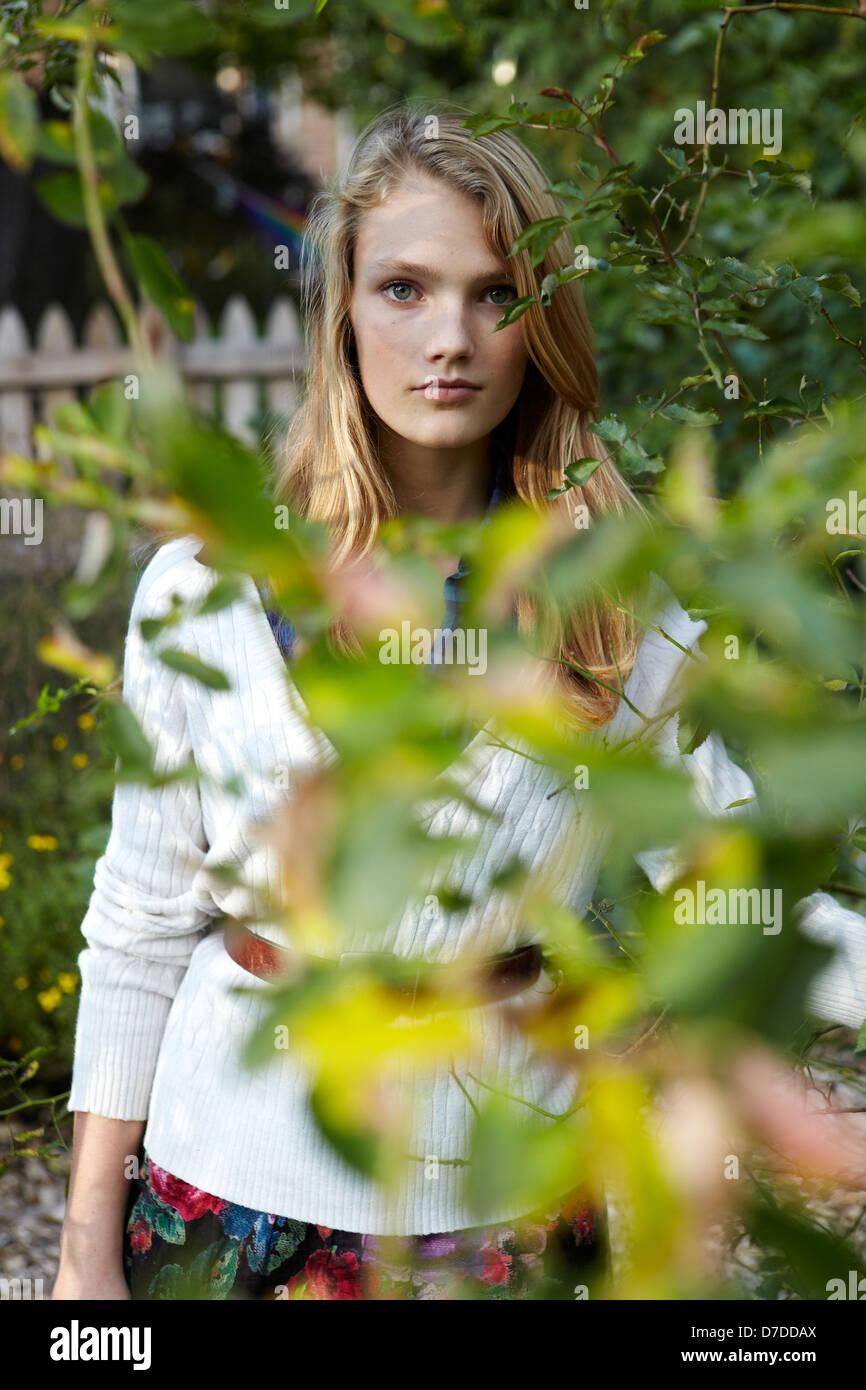 Hermosa teen detrás de árbol en el jardín Foto de stock