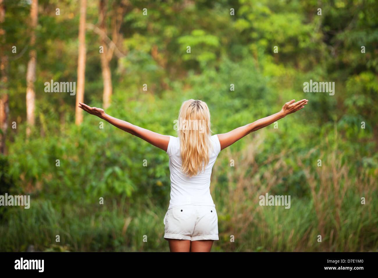 Armonía con la naturaleza, la espalda mujer con manos levantadas en el bosque Imagen De Stock
