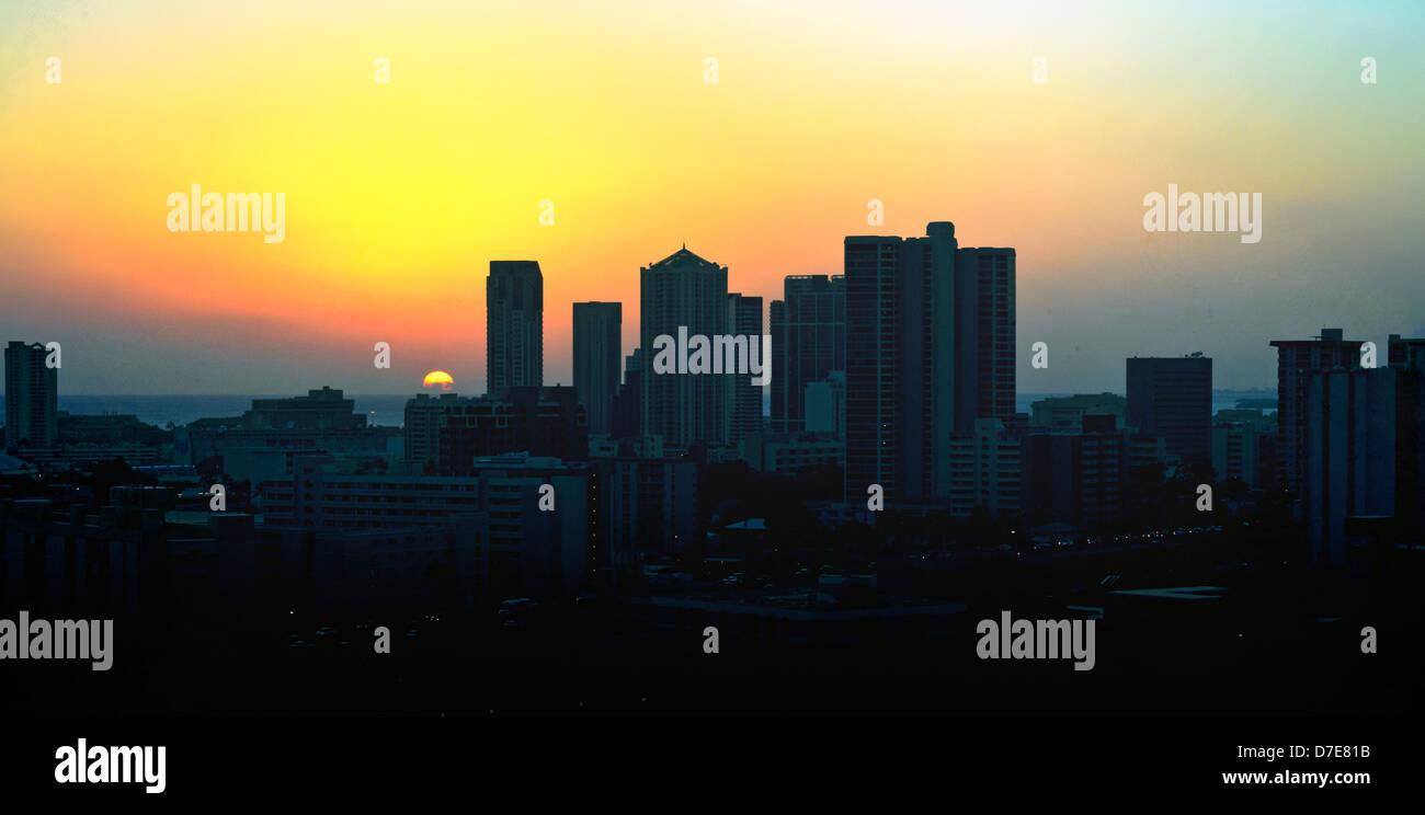 Último rayo de sol se esconde detrás de un horizonte de la ciudad Foto de stock