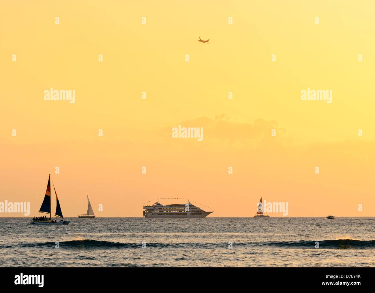 Varios barcos al mar fuera de Waikiki Beach para ver la hermosa puesta de sol hawaiana. Foto de stock