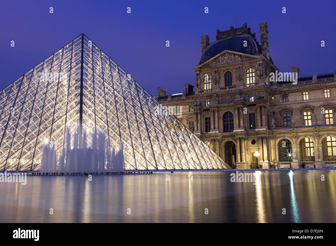 Museo del Louvre y la pirámide por la noche en París. Foto de stock