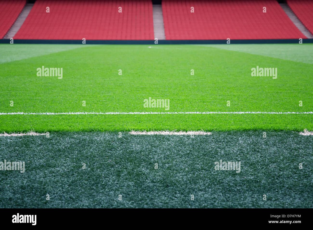 Campo de fútbol vacío con asientos rojos, el enfoque selectivo en la línea de banda. Foto de stock