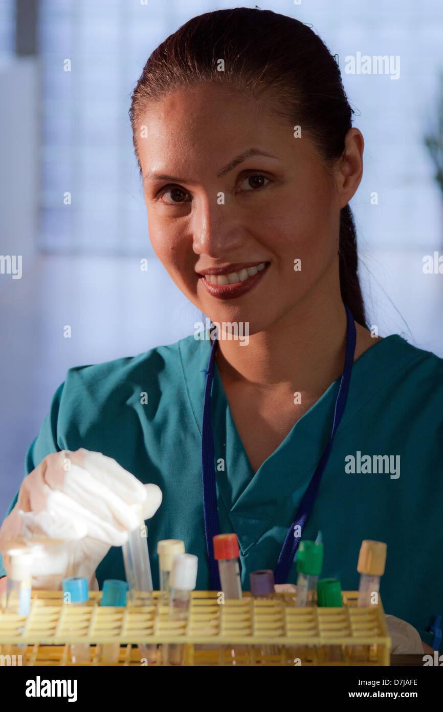 Retrato de enfermera, sujetando el tubo de ensayo, sonriendo Foto de stock