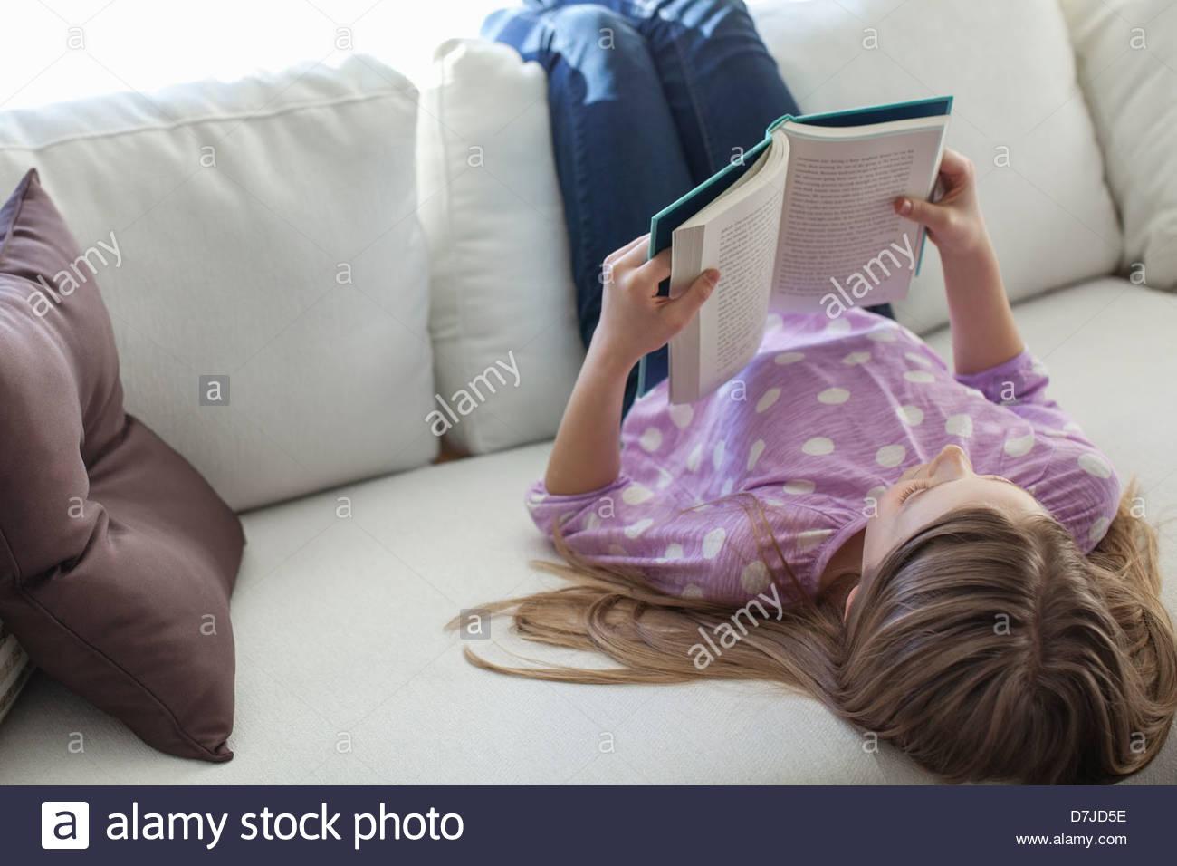 Libro de lectura joven tumbado en el sofá Imagen De Stock