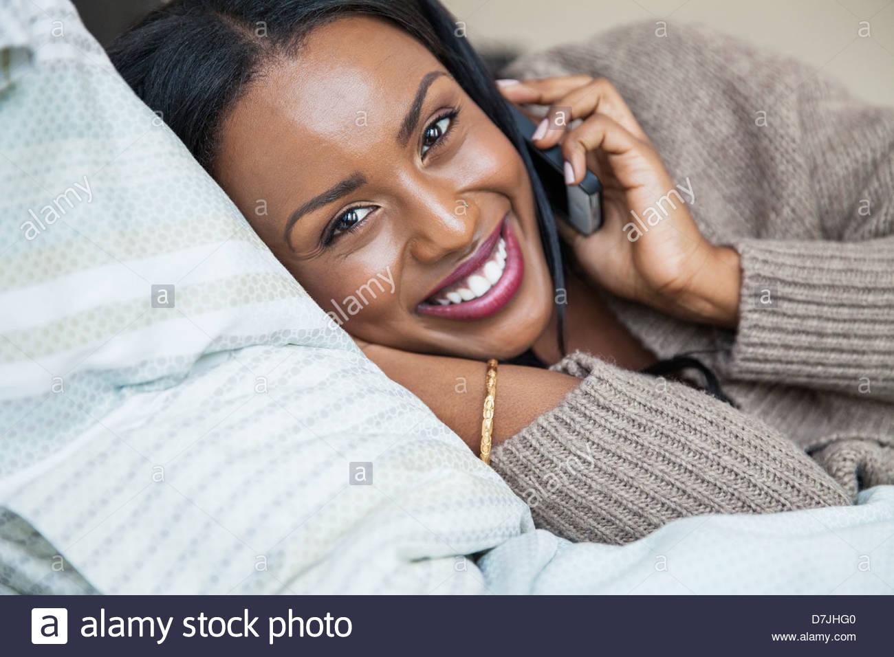 Retrato de mujer a través de teléfono móvil mientras está acostada en la cama Imagen De Stock