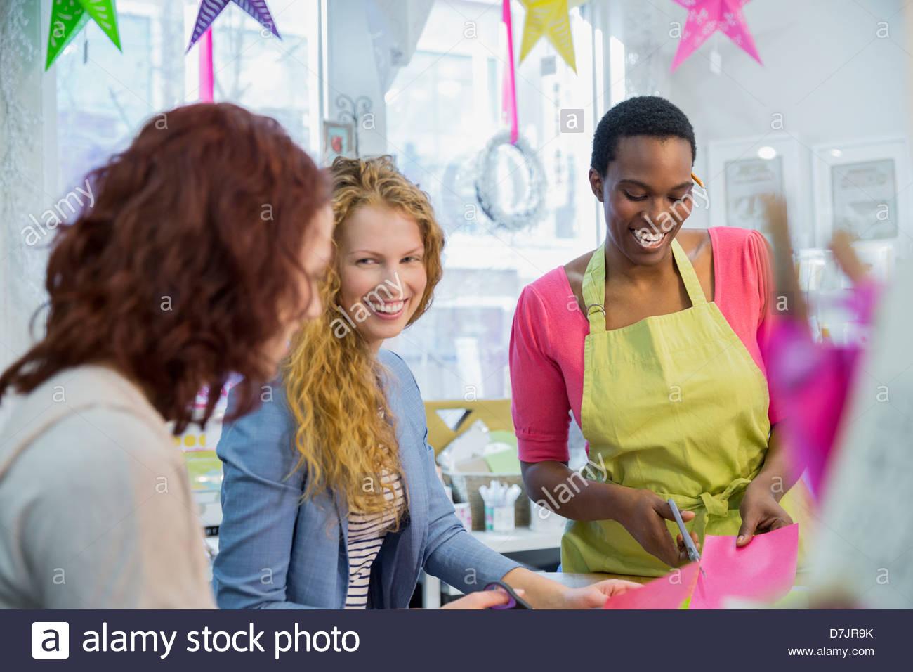 Hembra pequeño empresario enseñando a los clientes en la tienda Imagen De Stock