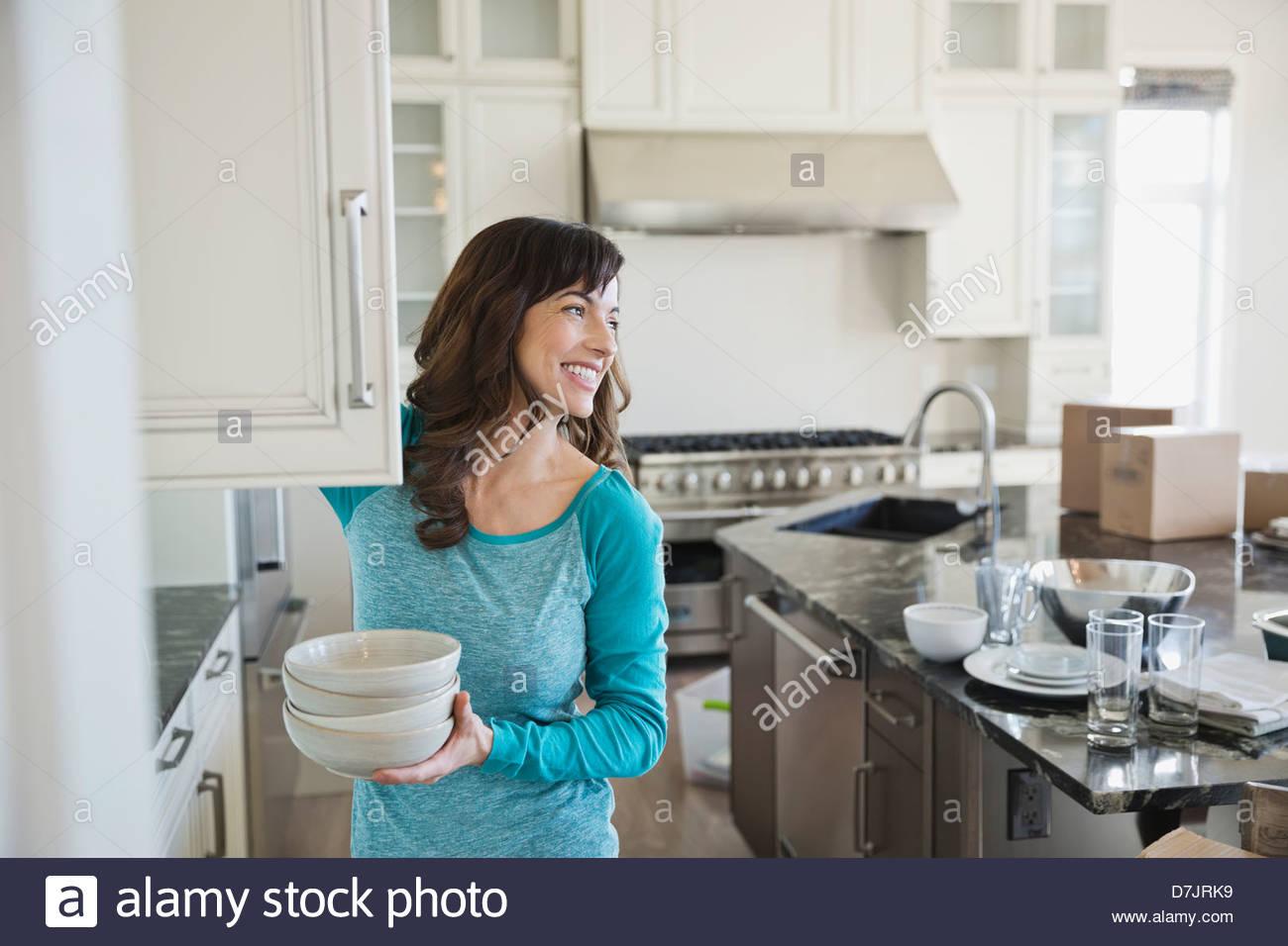 Mujer poniendo lejos los platos en el nuevo hogar Imagen De Stock