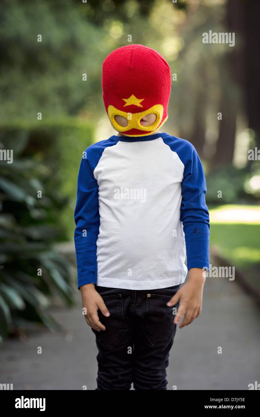 Niñito vestidos de rojo y amarillo Héroe Máscara posando fuera en la acera, oscureciendo sus ojos Imagen De Stock