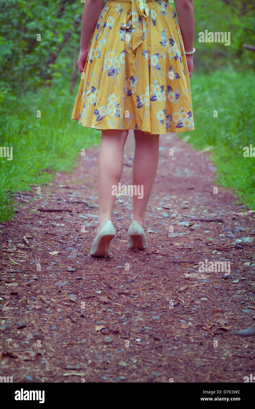 Las piernas de una mujer en un vestido amarillo caminando por un sendero en el bosque Imagen De Stock
